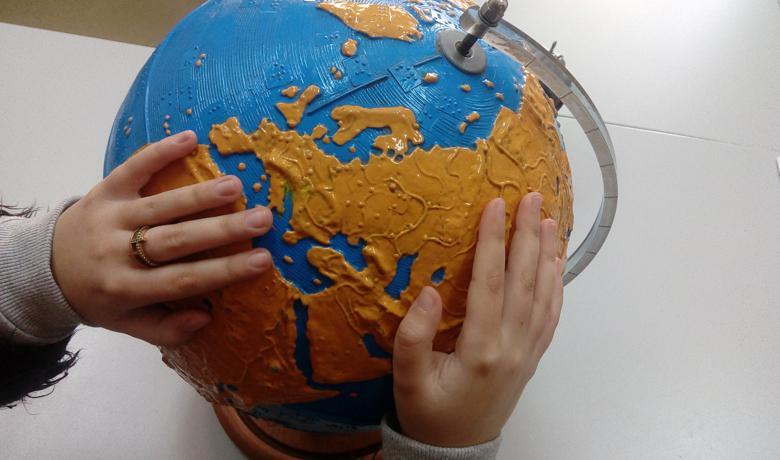 Χέρια μαθήτριας πάνω σε απτική υδρόγειο σφαίρα